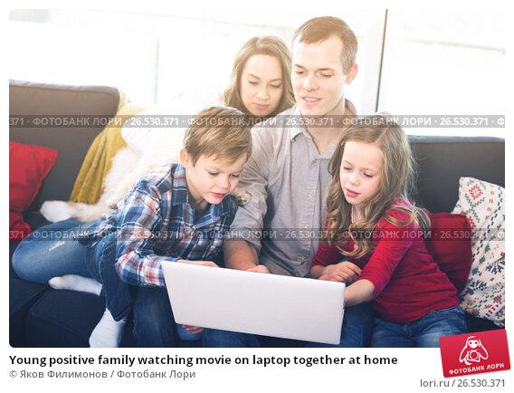 Купить «Young positive family watching movie on laptop together at home», фото № 26530371, снято 23 декабря 2016 г. (c) Яков Филимонов / Фотобанк Лори