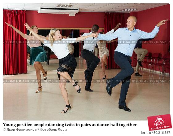 Купить «Young positive people dancing twist in pairs at dance hall together», фото № 30216567, снято 4 октября 2018 г. (c) Яков Филимонов / Фотобанк Лори