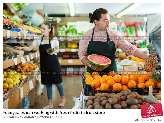 Купить «Young salesman working with fresh fruits in fruit store», фото № 30917167, снято 27 апреля 2019 г. (c) Яков Филимонов / Фотобанк Лори