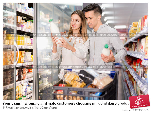 Young smiling female and male customers choosing milk and dairy products in grocery, family shopping. Стоковое фото, фотограф Яков Филимонов / Фотобанк Лори