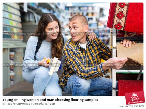 Young smiling woman and man choosing flooring samples. Стоковое фото, фотограф Яков Филимонов / Фотобанк Лори