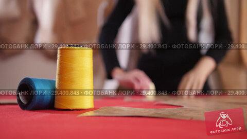 Купить «Young woman at sewing factory. A woman making sketches on the cloth. Sewing thread in focus», видеоролик № 29400843, снято 12 декабря 2018 г. (c) Константин Шишкин / Фотобанк Лори