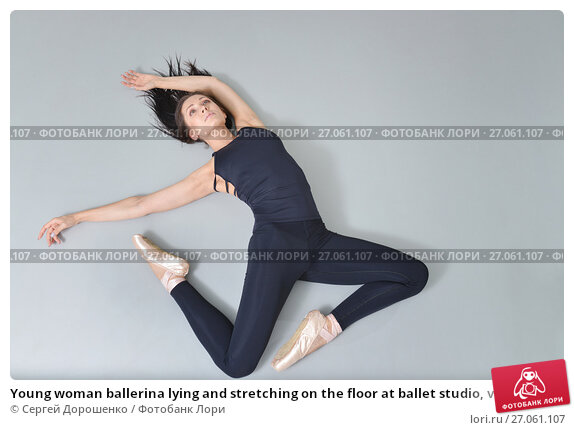Купить «Young woman ballerina lying and stretching on the floor at ballet studio, view from above», фото № 27061107, снято 11 декабря 2018 г. (c) Сергей Дорошенко / Фотобанк Лори