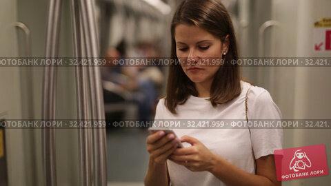Купить «Young woman browsing and typing messages on phone in subway car», видеоролик № 32421959, снято 19 сентября 2019 г. (c) Яков Филимонов / Фотобанк Лори