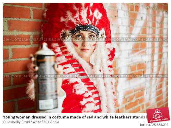 Купить «Young woman dressed in costume made of red and white feathers stands her back to the brick wall and holding spray can in outstretched hand», фото № 25838219, снято 13 февраля 2015 г. (c) Losevsky Pavel / Фотобанк Лори
