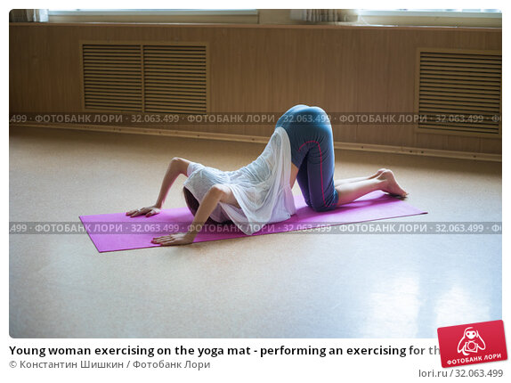 Young woman exercising on the yoga mat - performing an exercising for the loin and spine - bending her back down and leaning on the hands - chest touching the ground. Стоковое фото, фотограф Константин Шишкин / Фотобанк Лори