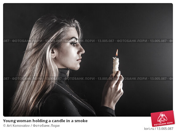 Купить «Young woman holding a candle in a smoke», фото № 13005087, снято 4 ноября 2015 г. (c) Art Konovalov / Фотобанк Лори