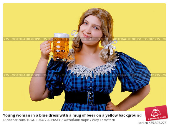 Young woman in a blue dress with a mug of beer on a yellow background. Стоковое фото, фотограф Zoonar.com/TUGOLUKOV ALEKSEY / easy Fotostock / Фотобанк Лори
