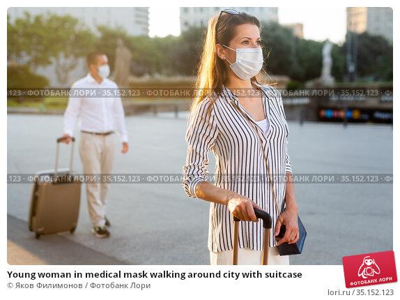 Young woman in medical mask walking around city with suitcase. Стоковое фото, фотограф Яков Филимонов / Фотобанк Лори