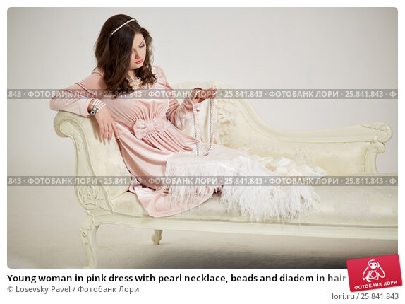 Купить «Young woman in pink dress with pearl necklace, beads and diadem in hair reclines on couch», фото № 25841843, снято 7 марта 2015 г. (c) Losevsky Pavel / Фотобанк Лори