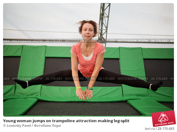 Купить «Young woman jumps on trampoline attraction making leg-split», фото № 28170683, снято 29 августа 2016 г. (c) Losevsky Pavel / Фотобанк Лори