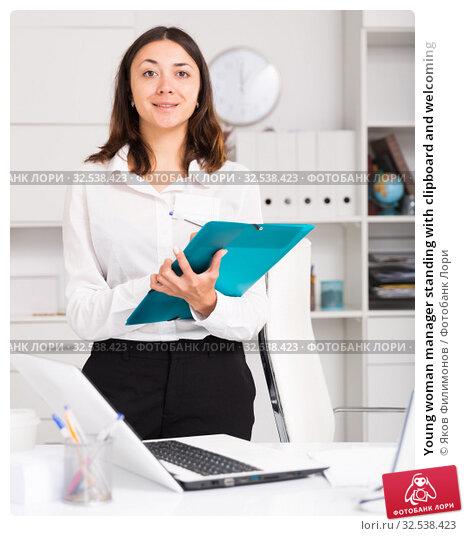 Купить «Young woman manager standing with clipboard and welcoming», фото № 32538423, снято 1 мая 2018 г. (c) Яков Филимонов / Фотобанк Лори