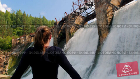 Young woman on vacation - walking near the water dam and looking around with her hands up. Стоковое видео, видеограф Константин Шишкин / Фотобанк Лори