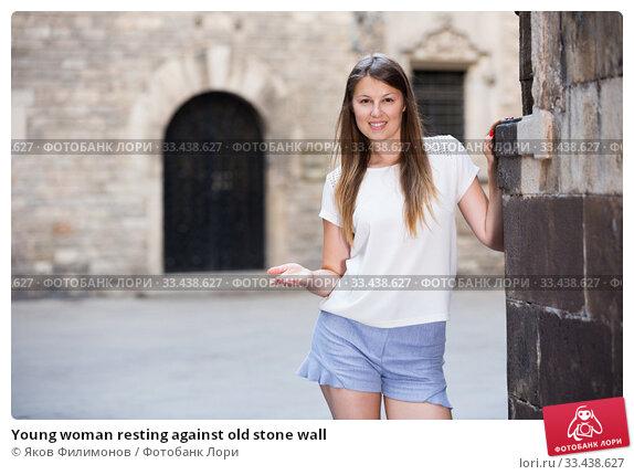 Купить «Young woman resting against old stone wall», фото № 33438627, снято 15 августа 2017 г. (c) Яков Филимонов / Фотобанк Лори