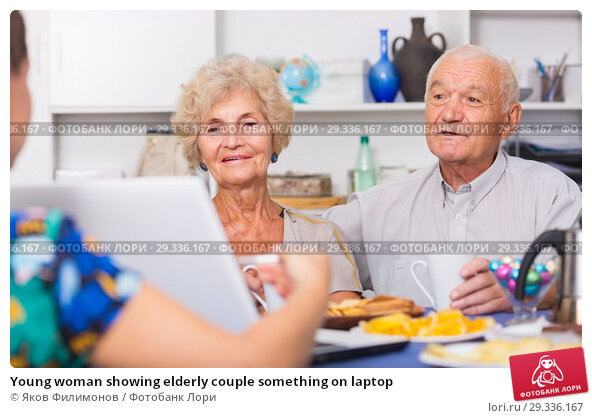 Young woman showing elderly couple something on laptop. Стоковое фото, фотограф Яков Филимонов / Фотобанк Лори