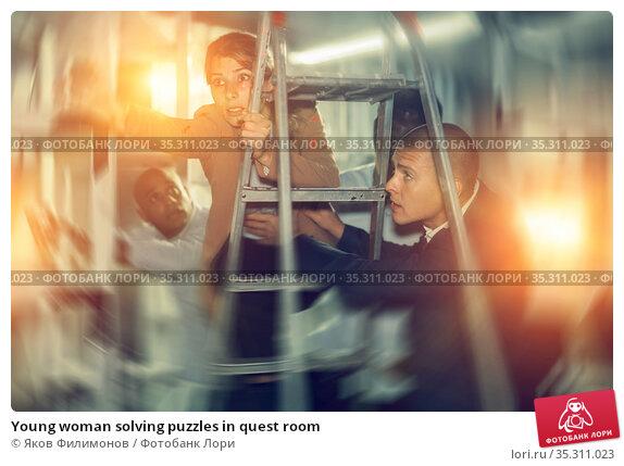 Young woman solving puzzles in quest room. Стоковое фото, фотограф Яков Филимонов / Фотобанк Лори