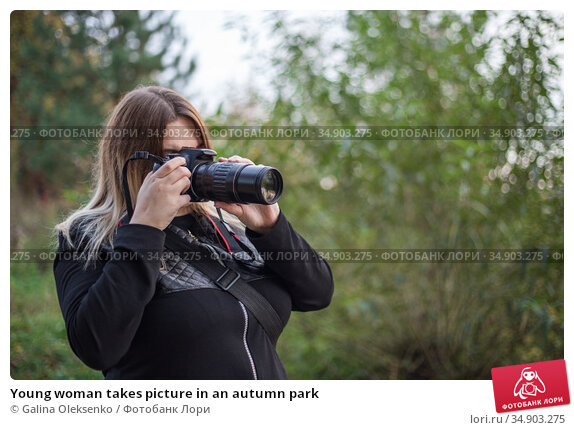 Young woman takes picture in an autumn park. Редакционное фото, фотограф Galina Oleksenko / Фотобанк Лори