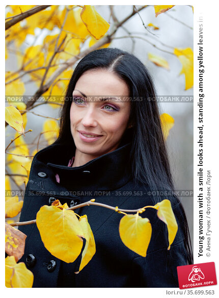 Young woman with a smile looks ahead, standing among yellow leaves in cold autumn weather. Стоковое фото, фотограф Анна Гучек / Фотобанк Лори