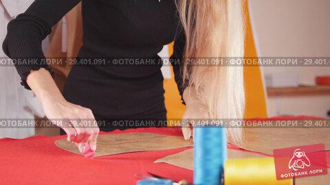 Купить «Young woman with arm prosthesis at sewing factory making sketches on the cloth. Sewing thread in focus.», видеоролик № 29401091, снято 10 декабря 2018 г. (c) Константин Шишкин / Фотобанк Лори