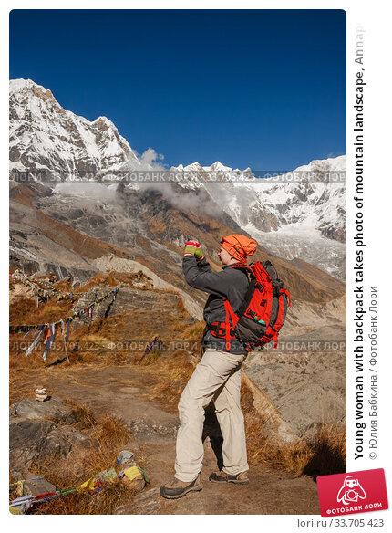 Купить «Young woman with backpack takes photo of mountain landscape, Annapurna Base Camp, Nepal», фото № 33705423, снято 8 октября 2012 г. (c) Юлия Бабкина / Фотобанк Лори
