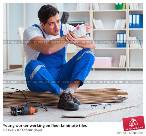Купить «Young worker working on floor laminate tiles», фото № 32205243, снято 9 марта 2017 г. (c) Elnur / Фотобанк Лори