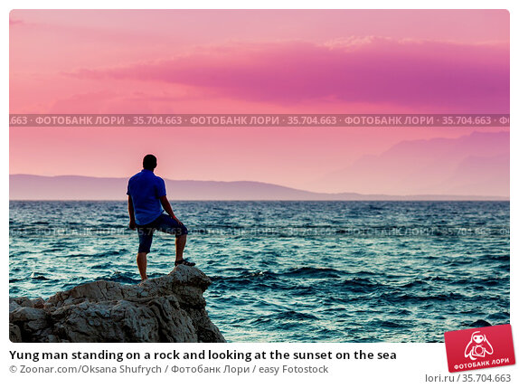 Yung man standing on a rock and looking at the sunset on the sea. Стоковое фото, фотограф Zoonar.com/Oksana Shufrych / easy Fotostock / Фотобанк Лори