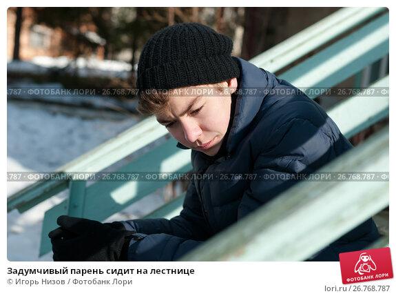 Купить «Задумчивый парень сидит на лестнице», эксклюзивное фото № 26768787, снято 25 февраля 2017 г. (c) Игорь Низов / Фотобанк Лори
