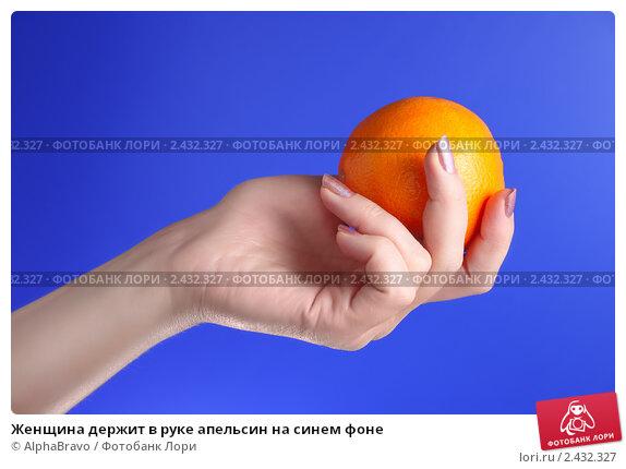 Купить «Женщина держит в руке апельсин на синем фоне», фото № 2432327, снято 26 мая 2019 г. (c) AlphaBravo / Фотобанк Лори