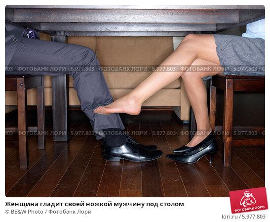 парень под столом ласкает ноги девушки