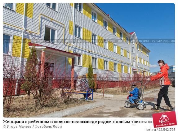 Купить «Женщина с ребенком в коляске-велосипеде рядом с новым трехэтажным многоквартирным домом», фото № 22542795, снято 8 апреля 2016 г. (c) Игорь Малеев / Фотобанк Лори