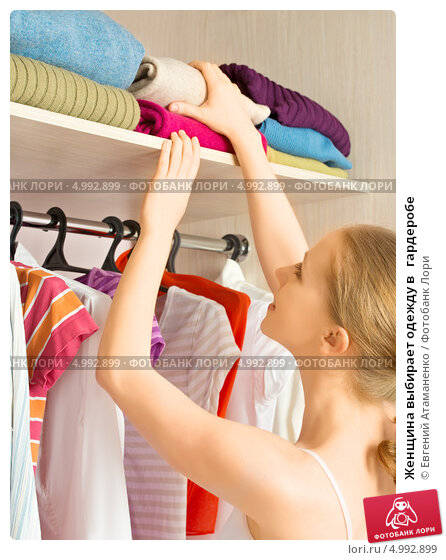 Купить «Женщина выбирает одежду в   гардеробе», фото № 4992899, снято 6 мая 2013 г. (c) Евгений Атаманенко / Фотобанк Лори