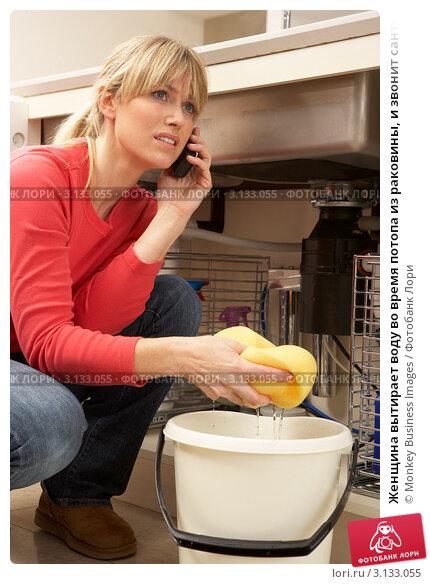 Купить «Женщина вытирает воду во время потопа из раковины, и звонит сантехнику по телефону», фото № 3133055, снято 5 января 2011 г. (c) Monkey Business Images / Фотобанк Лори