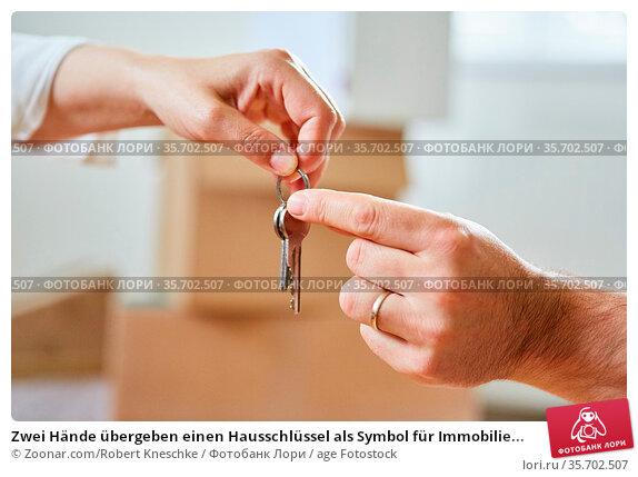 Zwei Hände übergeben einen Hausschlüssel als Symbol für Immobilie... Стоковое фото, фотограф Zoonar.com/Robert Kneschke / age Fotostock / Фотобанк Лори