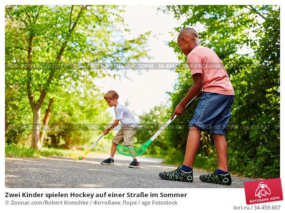 Zwei Kinder spielen Hockey auf einer Straße im Sommer. Стоковое фото, фотограф Zoonar.com/Robert Kneschke / age Fotostock / Фотобанк Лори