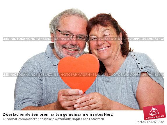 Zwei lachende Senioren halten gemeinsam ein rotes Herz. Стоковое фото, фотограф Zoonar.com/Robert Kneschke / age Fotostock / Фотобанк Лори