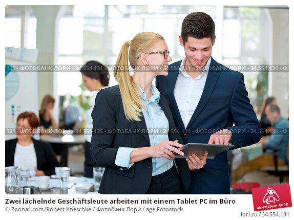 Zwei lächelnde Geschäftsleute arbeiten mit einem Tablet PC im Büro. Стоковое фото, фотограф Zoonar.com/Robert Kneschke / age Fotostock / Фотобанк Лори