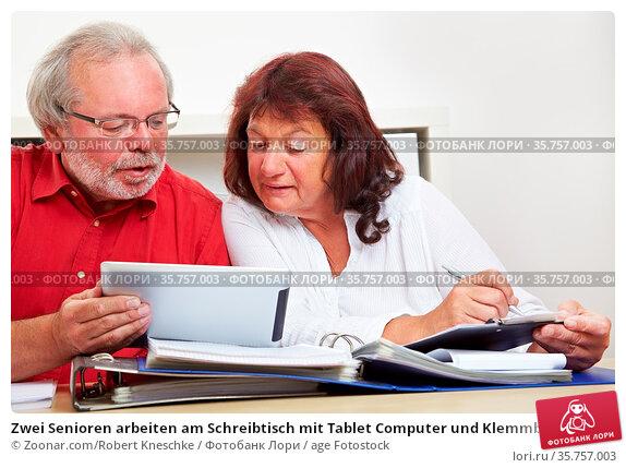 Zwei Senioren arbeiten am Schreibtisch mit Tablet Computer und Klemmbrett. Стоковое фото, фотограф Zoonar.com/Robert Kneschke / age Fotostock / Фотобанк Лори